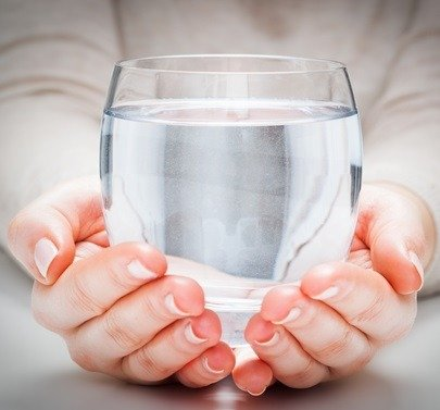 glass of clean mineral water in woman's hands